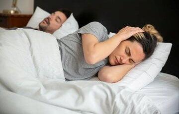 vrouw die wakker ligt van het snurken. Tips tegen snurken